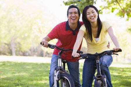 trail bike: Couple on bikes outdoors smiling