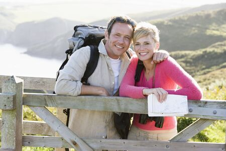 rambler: Couple on cliffside outdoors leaning on railing and smiling Stock Photo