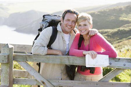 Paar auf cliffside im Freien am Gel�nder lehnt und l�chelnd Lizenzfreie Bilder - 3603691