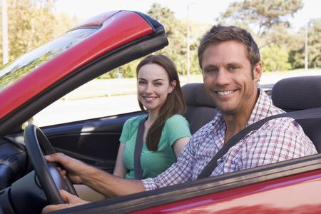 convertible car: Couple in convertible car smiling Stock Photo