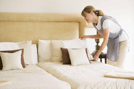 sirvienta: Haciendo de mucama cama en habitaci�n de hotel sonriente