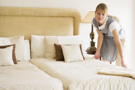 Maid machen Bett im Hotelzimmer