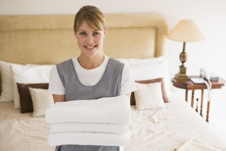 sirvienta: La celebraci�n de toallas de limpieza en la habitaci�n del hotel sonriente