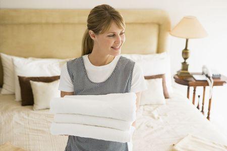 ama de llaves: La celebraci�n de toallas de limpieza en la habitaci�n del hotel sonriente