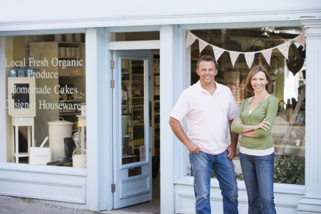 Couple standing in front of organic food store smiling photo