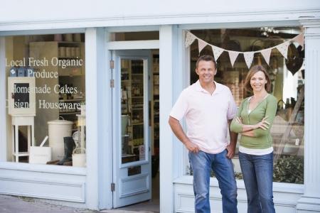 tiendas de comida: Joven de pie frente a tienda de comida org�nica sonriente Foto de archivo
