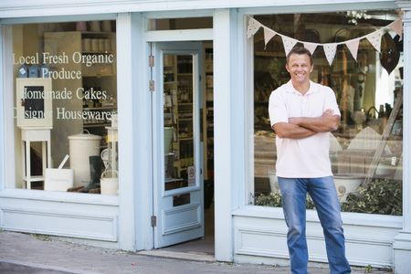 owner: Man standing in front of organic food store smiling Stock Photo