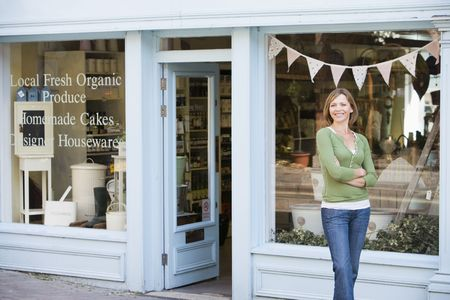 negocios comida: Mujer de pie en frente de la tienda de alimentos org�nicos sonriente  Foto de archivo