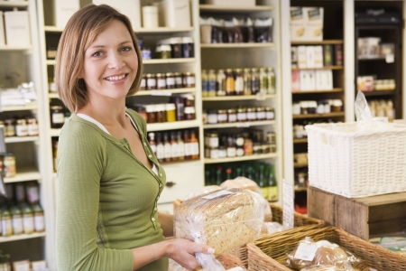 Woman in market looking at bread smiling photo