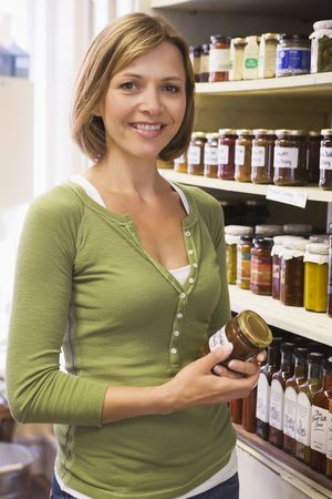 Woman in market looking at preserves smiling photo