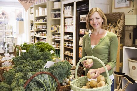 fresh produce: Woman in market looking at potatoes smiling Stock Photo