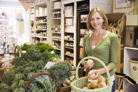 Woman in Markt Blick auf Kartoffeln lächelnd