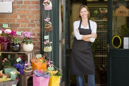 Donna che lavora in negozio di fiori sorridente  Archivio Fotografico