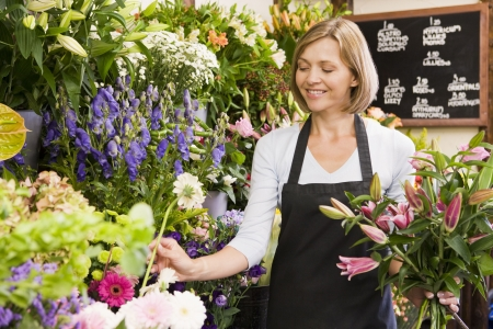 Woman working at flower shop smiling Stock Photo - 3726360