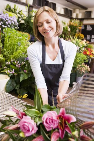 checkout stand: Woman working at flower shop smiling Stock Photo