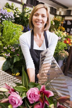 Woman working at flower shop smiling photo