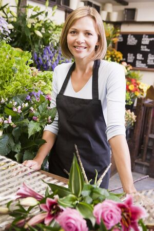 florists: Woman working at flower shop smiling Stock Photo