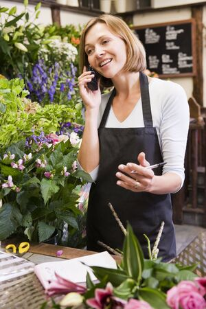 florists: Woman working at flower shop using telephone and smiling