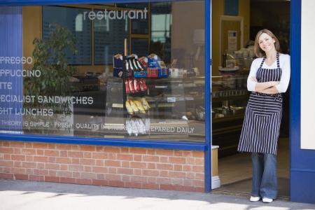 owners: Woman standing in doorway of restaurant smiling Stock Photo
