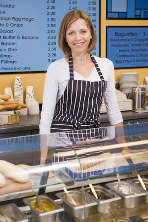 cafe shop: Woman standing at counter in restaurant smiling