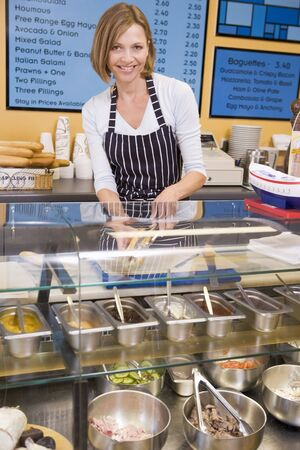 delicatessen: Woman standing at counter in restaurant smiling