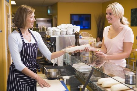 Woman standing at counter in restaurant serving customer and smiling Stock Photo - 3603487