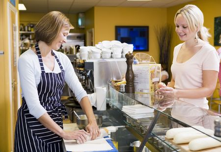 takeaway: Woman standing at counter in restaurant serving customer smiling
