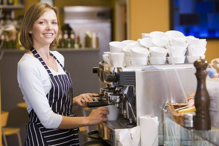 coffee machine: Woman making coffee in restaurant smiling