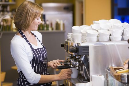 Woman making coffee in restaurant smiling photo