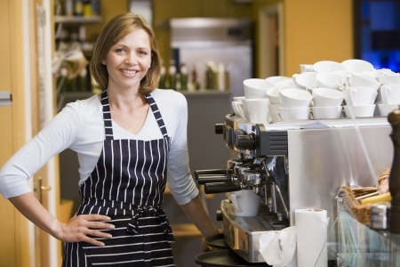 making coffee: Woman making coffee in restaurant smiling
