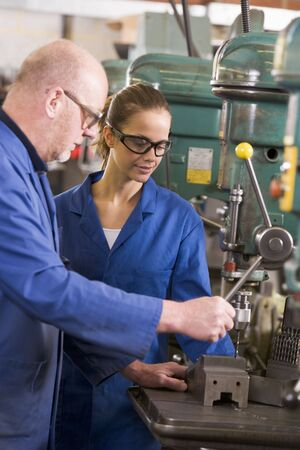 Two machinists working on machine photo