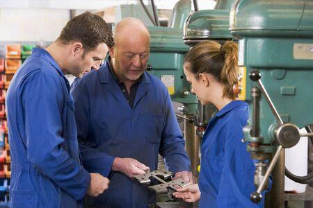 apprenti: Trois machinistes en travail ? la machine ? parler