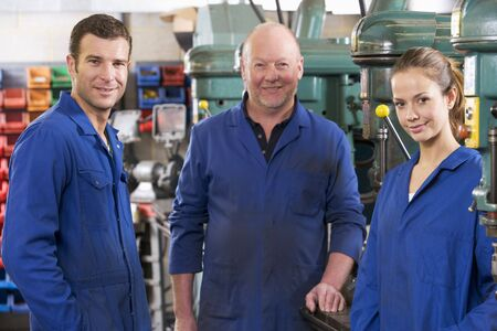 Three machinists in workspace by machine talking photo