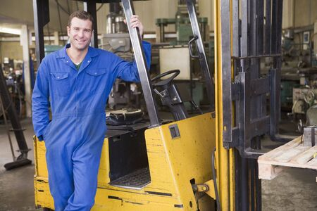 tradesperson: Warehouse worker standing by forklift
