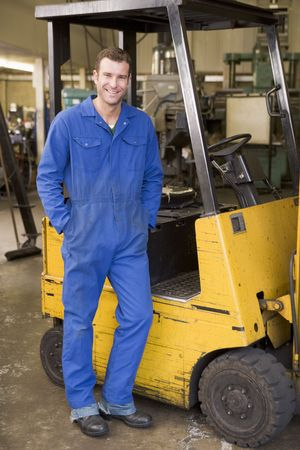 forklift truck: Warehouse worker standing by forklift