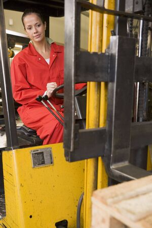 overalls: Warehouse worker in forklift Stock Photo