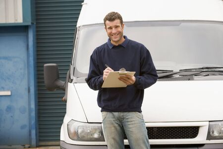 Deliveryperson standing with van writing in clipboard smiling photo