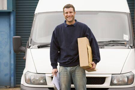 Deliveryperson permanent avec van presse-papiers et le sourire de la zone de détention Banque d'images
