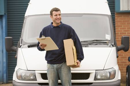 delivery driver: Deliveryperson standing with van holding clipboard and box smiling