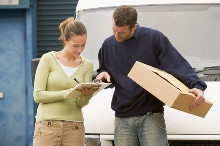 Two deliverypeople standing with van holding clipboard and box photo