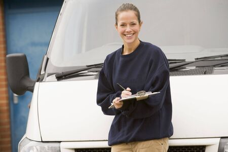 delivery driver: Deliveryperson standing with van writing in clipboard smiling