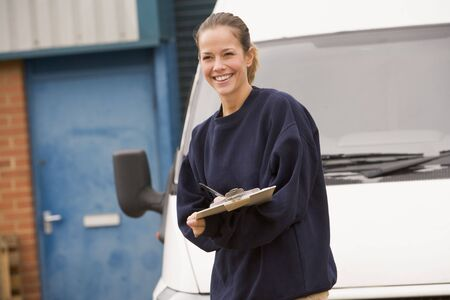 delivery van: Deliveryperson standing with van writing in clipboard smiling