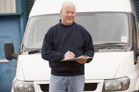 Deliveryperson standing with van writing in clipboard photo