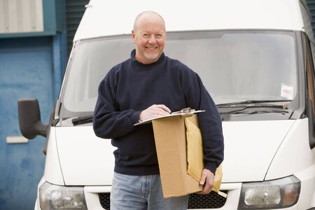 Deliveryperson standing with van with clipboard and box smiling photo