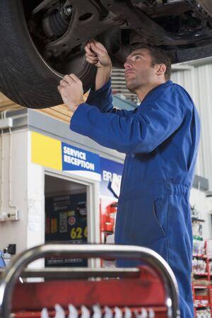 Mechanic working under car photo