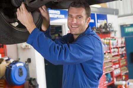 servicing: Mechanic working under car smiling