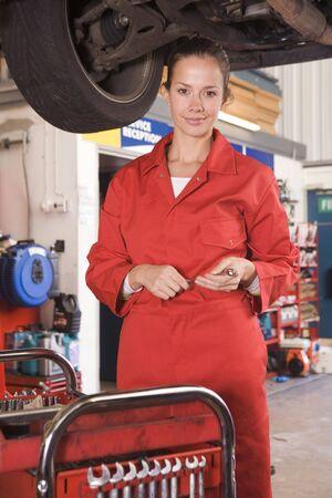 Mechanic working under car smiling photo