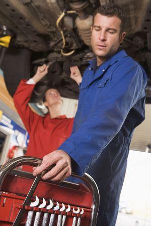 tradesperson: Two mechanics working under car