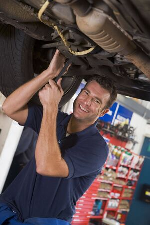 Mechanic working under car smiling Stock Photo - 3602868