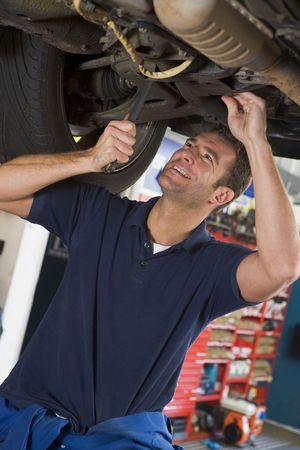 mecanico automotriz: Mec�nico de coches que trabajan bajo sonriente  Foto de archivo